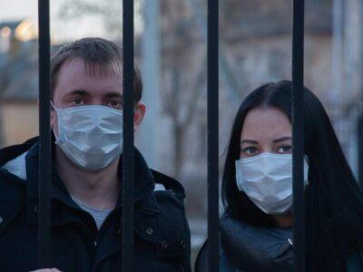 Dwoje mieszkańców DPS stoi w maseczkach za bramą.